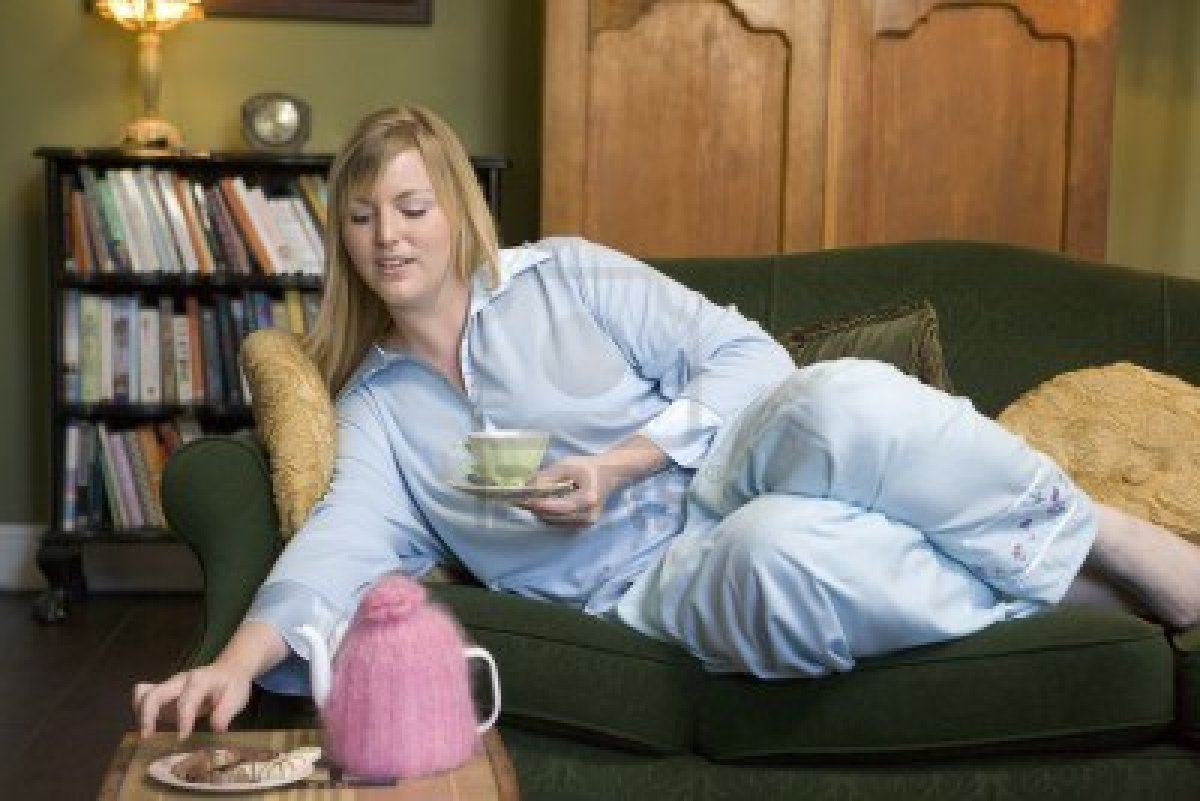 3226317-young-woman-lying-on-sofa-at-home-eating-cookies-and-drinking
